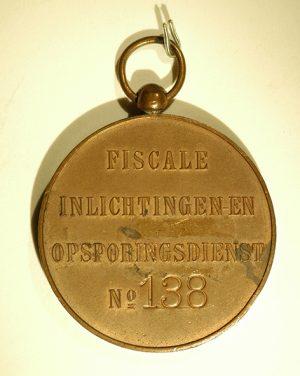 Op de foto ligt een goudkleurige penning op een witte ondergrond. Op de penning zijn de woorden Fiscale Inlichtingen en Opsporingsdienst gegraveerd. En no. 138.