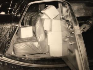 Een zwart wit fot van een donkere auto met openstaand portier, waarvan de hele achterbank is volgepropt met grote witte blokken boter.