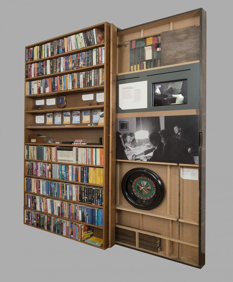 Achter een volle houten boekenkast is een ingeklapte roulettetafel te zien, met een zwartwit foto van hoe de tafel in gebruik is door 5 mannen in pak en 1 dame.