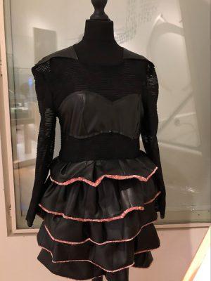 Op een zwarte paspop hangt een zwarte jurk van gaas en kunstleer, met een rok van met roze biezen afgewerkte ruches. en