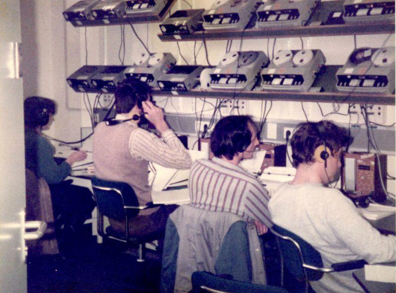 Voor een wand met bandrecorders zitten 4 personen naast elkaar op een rij met koptelefoons op te luisteren.